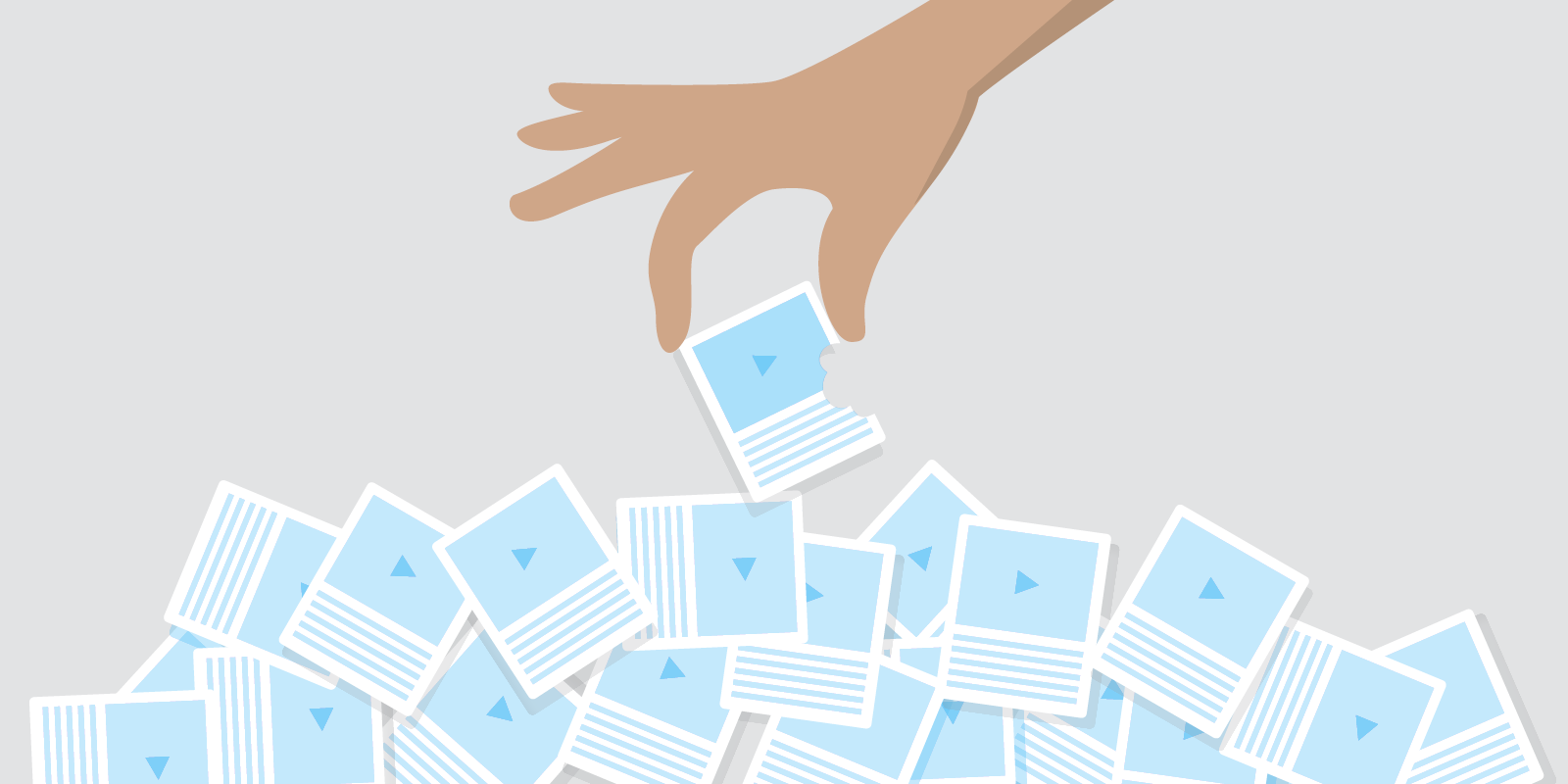 Hand reaches into a pile of content cards with videos and descriptions. Lifts a card with a bite in it.